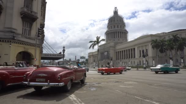 Movement retro cars, local autos and vehicles are riding near ancient colonial Capitol building in a central empty crossroad of Havana city