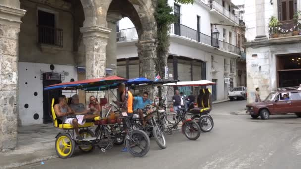 Trishaws with drivers are parked in the parking zone near ancient colonial building of Havana and waiting for a passengers