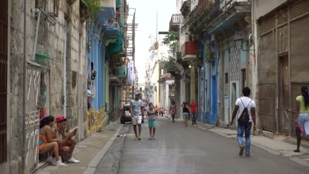 Young latino man with junior brother are walking on street of Havana at summer day