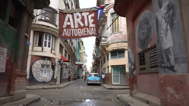 Walls with colorful historical picture of revolution time on the central streets of Havana at summer rainy day