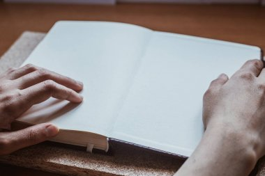 Female hands holding diary on the wooden desk. With space for text