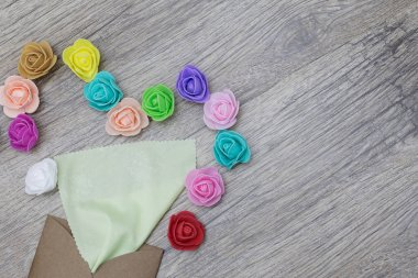 A bright green napkin sticks out of the craft envelope. Decorated in shape of heart with multi-colored roses. Flat lay image.
