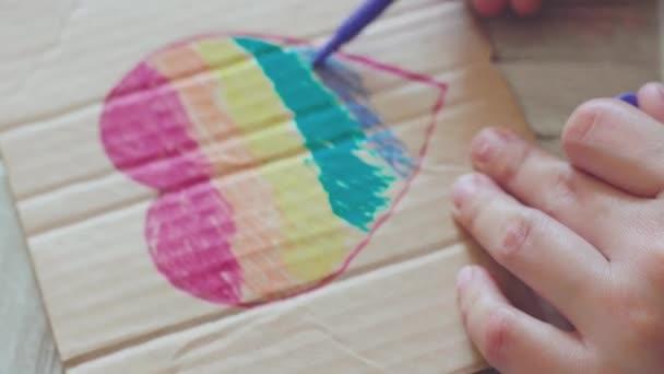 Den pýchy2020. Žena kreslí duhovou vlajku na karton. Příprava plakátu s duhovými malířskými prvky pro každoroční pochod LGBTQ. LGBTQ Pride Festival2020. Lidská práva, koncepce rovnosti pohlaví