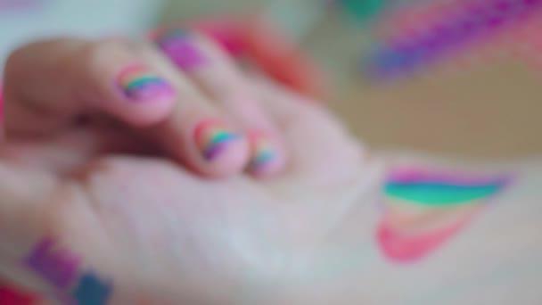 Den pýchy. Žena si na nehty kreslí duhovou vlajku. LGBTQ styl nehtů umění a tělo umění. Festival pýchy2020. Lidská práva, koncepce rovnosti pohlaví