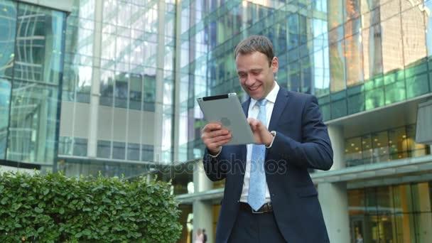 Pohledný podnikatel používající počítač tabletu na ulici, usměvavý, smích