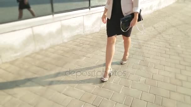 Pretty girl walking in high heels down the street in the sun. Steadicam shot.