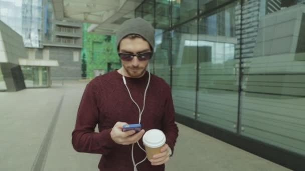 Hezký bokovky pomocí aplikace a poslechu hudby ve sluchátkách smartphone, pití kávy a procházky