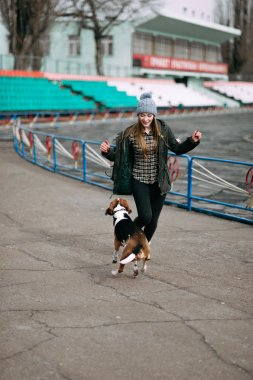Young hipster girl with her pet estonian hound dog playing, junping and hugging and having fun outdoor at the old stadium.