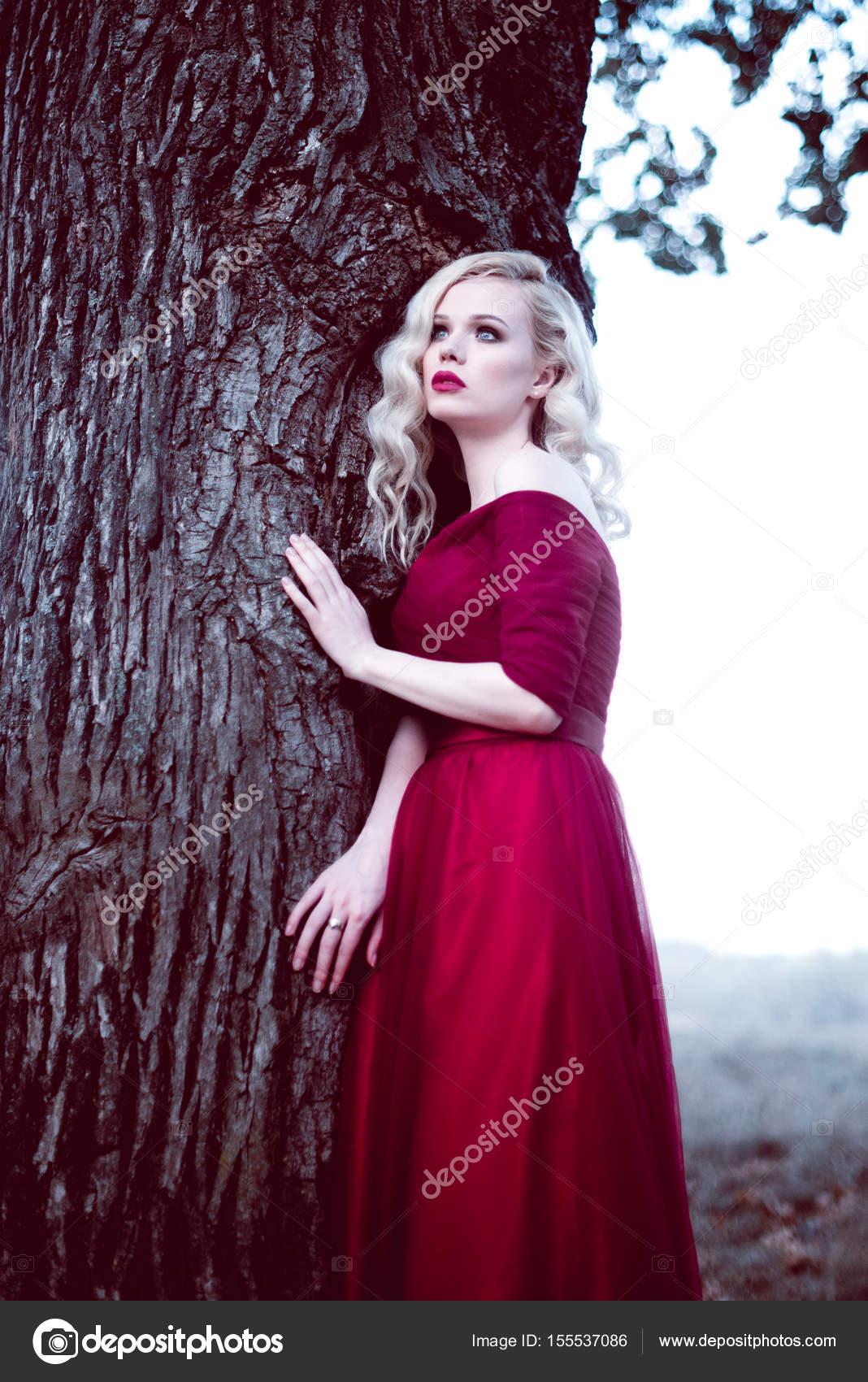 Moda hermosa rubia joven en hermoso vestido rojo en un bosque de ...