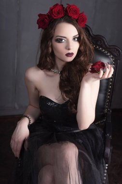 beautiful young woman with roses flower in hair, wearing black dress with make-up over dark background, gothic atmosphere. dark red lips.close-up fashion retouched portrait