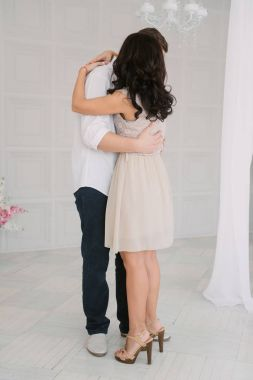 Young cheerful european couple in love embracing and kissing in decorated studio, light pastel colors, dating.