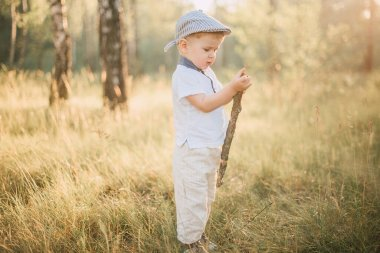 Portrait of a happy cute little boy having fun outdoors, exploring summer nature forest