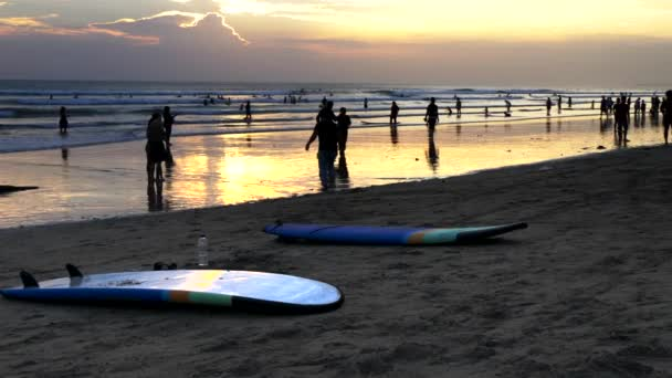 sunset shot of two surfboards laying on the beach at kuta beach