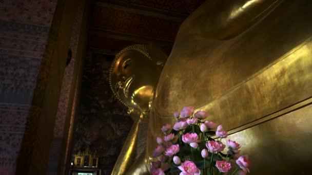 széles kilátás nyílik a fekvő buddha virágokkal az előtérben, bangkok