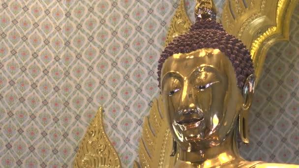 záběr zblízka na hlavu sochy buddhy z ryzího zlata v chrámu Wat Traimit