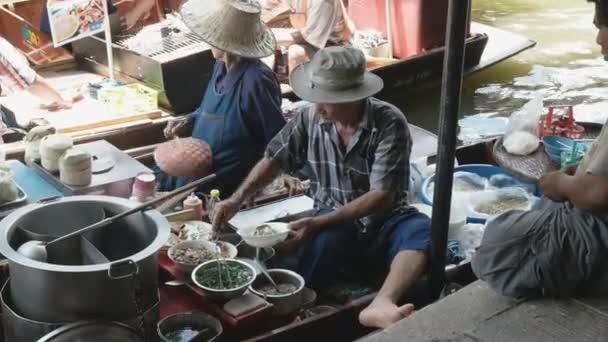 BANGKOK, THAILAND- JUNE, 23, 2017: a thai man cook serves food from a boat at damnoen saduak floating marke