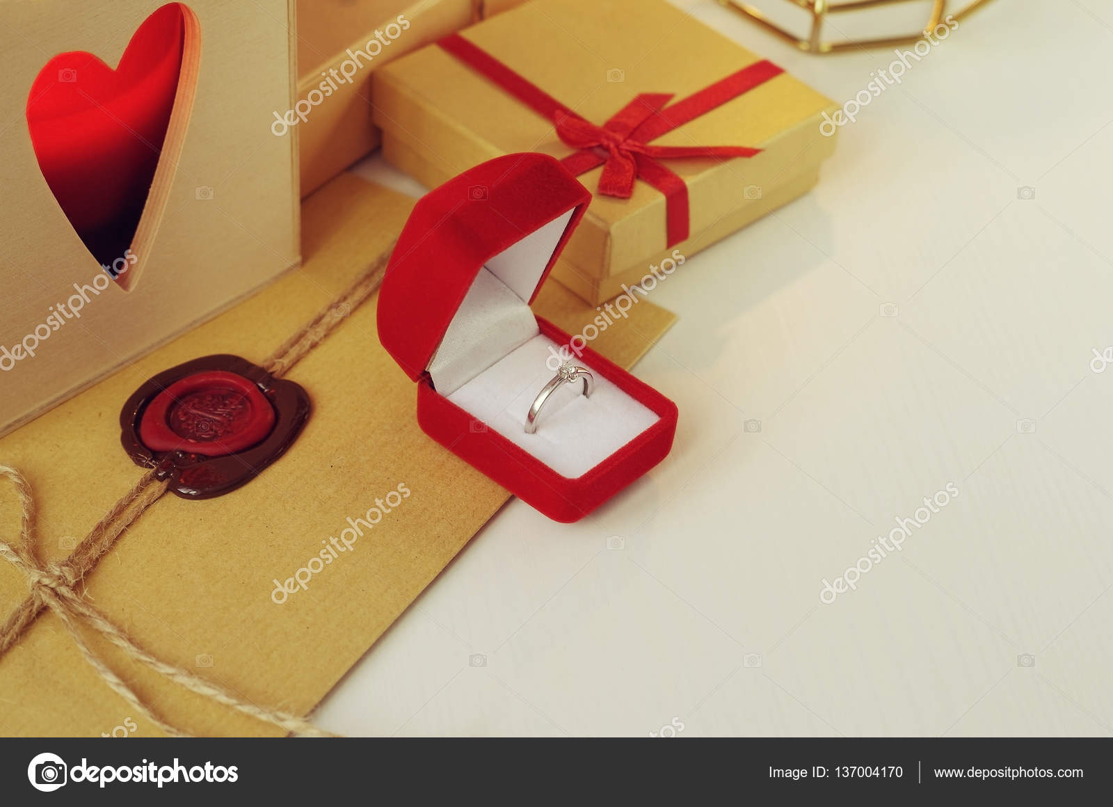 Engagement diamond ring in a red velvet box. Envelope with wax seal ...