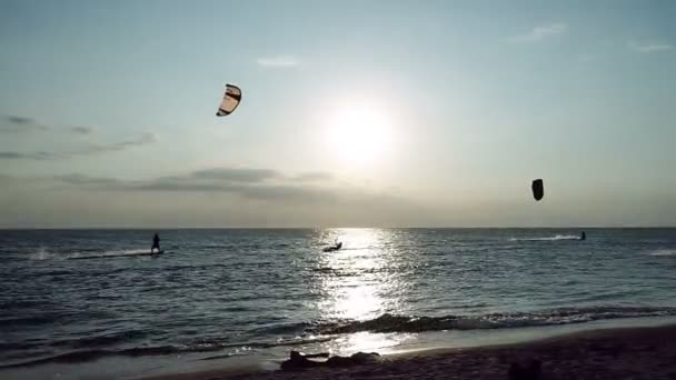 Kitesurfing. Five kitesurfers going surfing on the surfboards on waves at sunset. HD