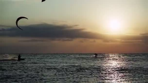 Kitesurfing. Silhouettes of four surfers riding on boards on the surface of waves and jumping with kite at sunset. Azov sea. HD