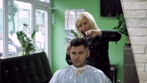 Hajvágás a fodrásznál. Gyönyörű szőke nő vágás férfi Sötét haja. HD