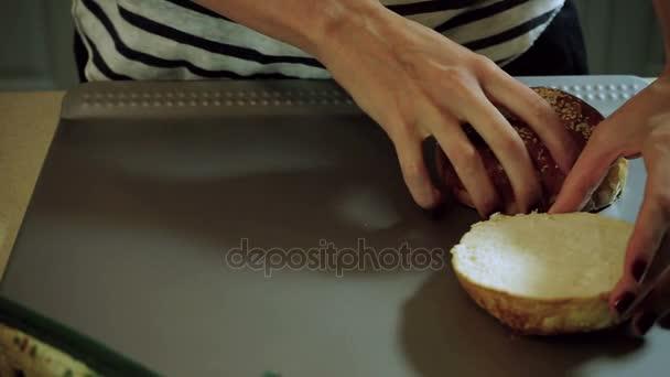 Vaření hamburger. Ženské ruce rozložení tři řezu chleba rolích na stůl. HD
