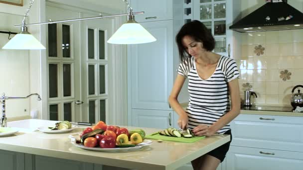 Wide shoot of beautiful brunette woman cutting vegetables at the kitchen. HD