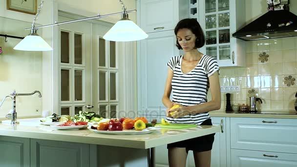 Celé natáčení krásná bruneta žena krájení zeleniny v kuchyni. HD
