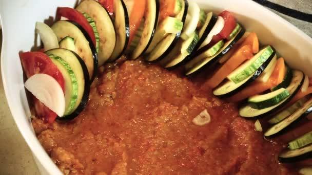 Vaření ratatouille. Ženské ruce rozložení nakrájenou zeleninu do pekáčku. HD