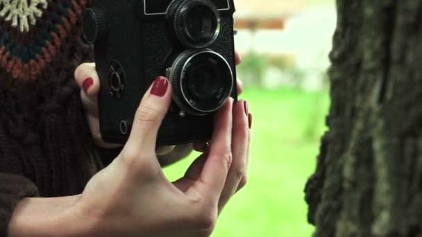 Eine junge Frau fotografiert mit einer alten Oldtimer-Filmkamera im Herbstpark. hd