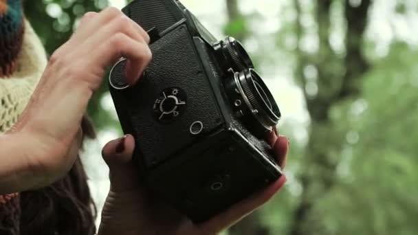 Mladá žena je fotografování na staré retro film fotoaparát v podzimním parku. HD