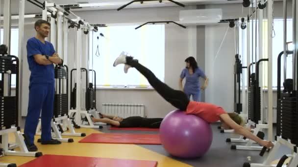 eine Gruppe von Menschen, die an Trainingsgeräten mit individuellen Trainern im Fitnessstudio trainieren. hd