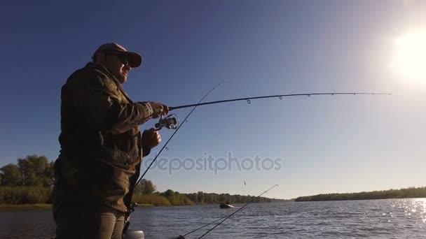 Malebná krajina. Mladý muž je lov ryb stoje na motorovém člunu. 4k