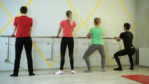 Egy embercsoport gyakorló gyakorlatok a torna edző sportcsarnokban. HD