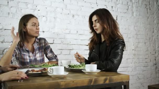Tři kamarádky jíst jídlo, smát, bavit a mluví v kavárně. HD