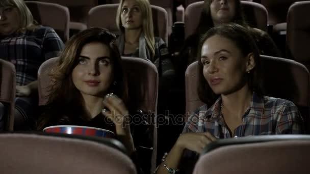 Mozi. Három csinos női meg filmnézésre és pattogatott kukoricát eszik a moziban. HD