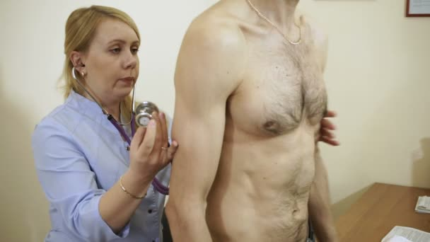 Female doctor listening to patients chest and back with stethoscope in her office at the hospital. HD