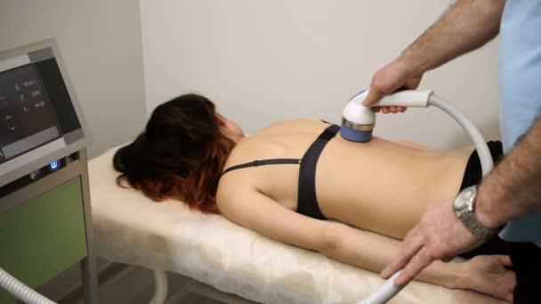 der Physiotherapeut, der den Rücken einer Frau mit Geräten zur Stoßwellentherapie behandelt. hd