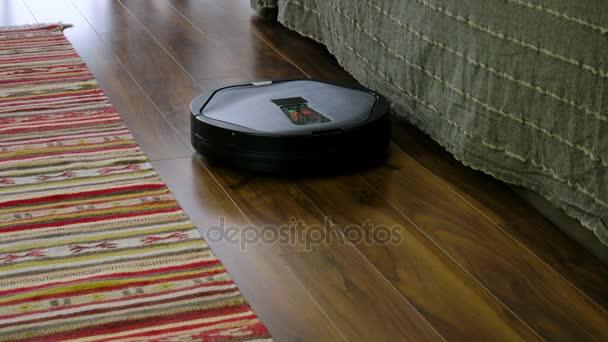 der Roboterreiniger reinigt den Laminatboden im Raum. 4k