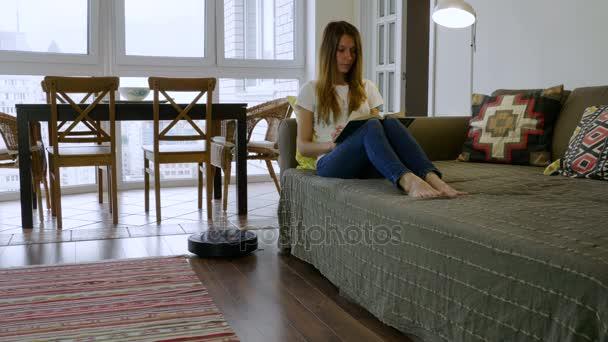 Mladými, krásnými žena čte knihu zatímco automatický vysavač na čištění podlahy v místnosti. 4k