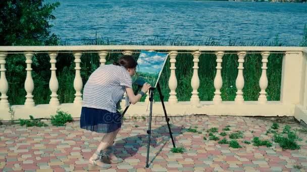Malíř-krajinář. Mladá žena Malování přírodní scenérie s olejovými barvami. 4k