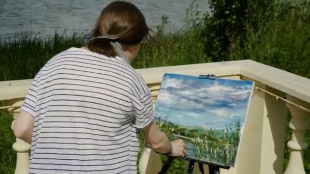 Malíř-krajinář. Pohled ze zadní strany žena Malování přírodní scenérie s olejovými barvami. 4k