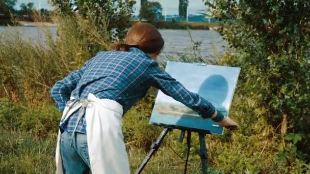 Pohled ze zadní strany malíř Malování krajiny s olejovými barvami. 4k