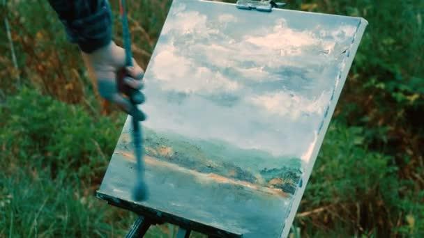 Zenske ruce Malování s olejovými barvami pomocí štětcem vodní krajina. 4k