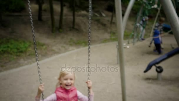 A positive smiling little girl laughing during swinging on a swing at childrens playground. Slow Motion. HD