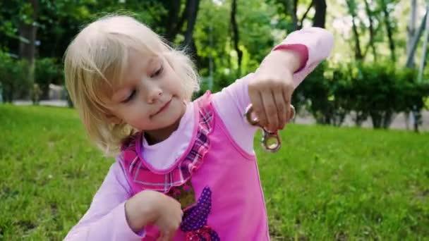 La piccola ragazza sorridente bionda giocando con il giocattolo di spinner fidget nel parco in una giornata di sole. 4k