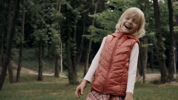 Positive emotions. Little cute blond girl smiling, fooling around and happy laughing in a summer park. Slow motion. HD
