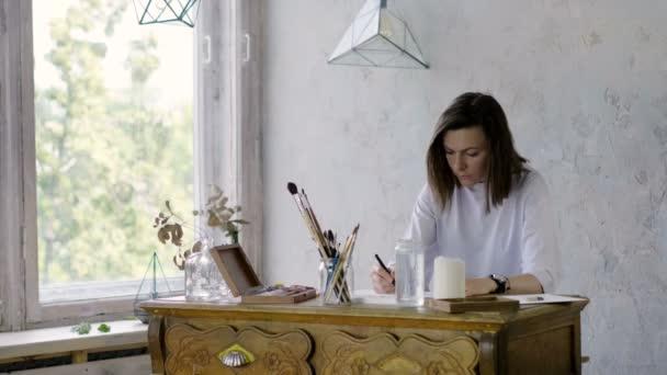 Malerei im Atelier. Die hübsche, dunkle Künstlerin zeichnet mit Bleistift auf einem Papier am Holztisch. 4k