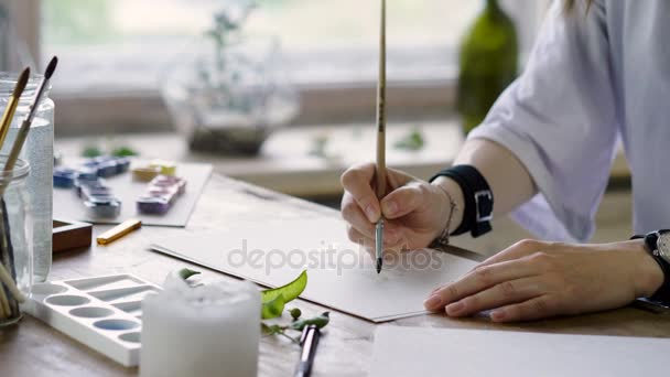 Close-up shot of unknown female artists hands painting with watercolors a picture. 4K