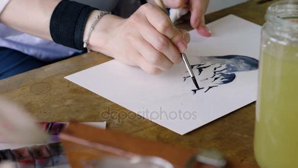 Detailní záběr umělců ruce malování ptáků na modré srdce v akvarely pomocí štětcem v ateliéru. 4k