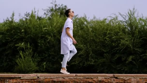 Moderní žena tanečnice tančí nahoře červená cihlová zeď na ulici. 4k